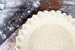 Macro of Homemade Butter Pie Crust in Pie Plate. Homemade butter pie crust in pie plate with fluted pinched edge, rolling pin and extra ball of dough over stock photos