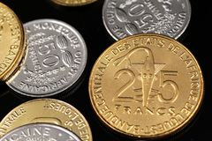 A close up image of West African Franc coins on a black background. A macro image of an assortment of West African Franc coins on a reflective black background stock image
