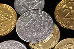 A close up image of West African Franc coins on a black background. A macro image of an assortment of West African Franc coins on a reflective black background royalty free stock photos