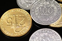 A close up image of West African Franc coins on a black background. A macro image of an assortment of West African Franc coins on a reflective black background royalty free stock photo