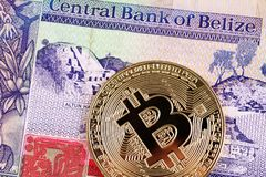 Close up image of a Belize two dollar bill with a close up of a golden bitcoin. A macro image of a Belize two dollar bill with a golden bitcoin close up royalty free stock photography