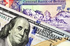 A two dollar bill from Belize with an American one hundred dollar bill. A macro image of a Belize two dollar bill in macro with a blue American one hundred royalty free stock photo