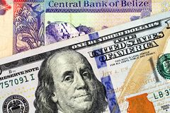 A two dollar bill from Belize with an American one hundred dollar bill. A macro image of a Belize two dollar bill in macro with a blue American one hundred stock image