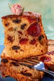Macro image of a cake slice with fruits and a decor of tea rose. Fruit cake with raisin. stock photo