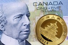 A Canadian five dollar bill with a Chinese gold coin close up royalty free stock photo