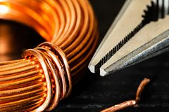Macro Image of a coil of copper wire and a pair of needle-nose pliers stock photos