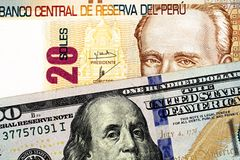 A close up up image of a Peruvian bank note with an American one hundred dollar bill royalty free stock photos