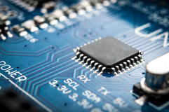 Macro image of a computer chip. Integrated semiconductor microchip/ microprocessor on blue circuit board representative of the high tech industry and computer Royalty Free Stock Photo