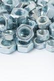 Macro image de la pile des écrous gris en métal au-dessus du fond blanc Image stock