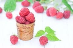 Macro image of fresh raspberry in the old wooden cup on white ta. Macro image of fresh raspberry  in the old wooden cup on white table Stock Photo