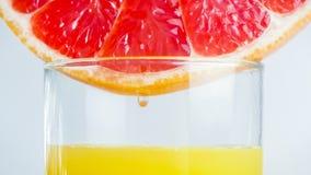 Macro image of fresh grapefruit slice in glass of juice royalty free stock photos