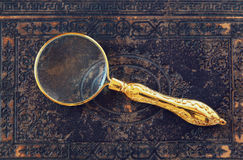 Macro image of magnifying glass over antique black cover Royalty Free Stock Images