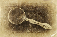 Macro image of magnifying glass over antique black cover. retro filtered image, old style photo. ץ Stock Photo