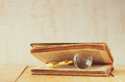 Macro image of magnifying glass over antique open book. Stock Photography