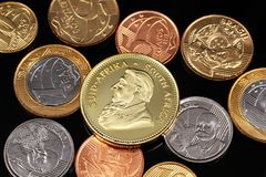 An assortment of Brazilian coins on a black reflective background with a South African one ounce gold Krugerrand coin. A macro image of miscellaneous Brazilian royalty free stock photos