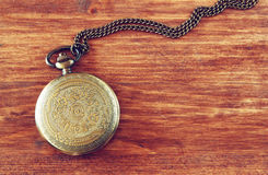 Macro image of old vintage pocket watch on wooden table. top view Royalty Free Stock Photos