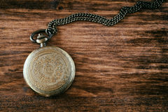 Macro image of old vintage pocket watch on wooden table. top view. retro filtered image Royalty Free Stock Images