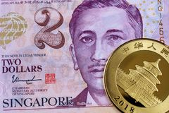 A Singapore two dollar note with a Chinese gold coin stock photos