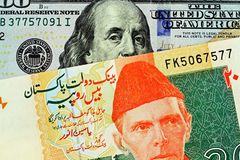 A close up image of a Pakistani rupee bank note with an American one hundred dollar bill royalty free stock photo