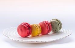 Macro immagine dei macarons colourful su un piatto bianco Immagine Stock