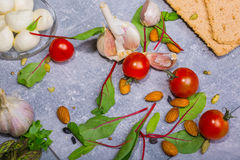 Macro immagine dei pomodori ciliegia, delle foglie dell'insalata verde, dell'aglio e delle patate Ingredienti per l'insalata di e Fotografie Stock