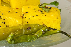 Macro of Indian Snacks Dhokla with fried chillies Royalty Free Stock Photos