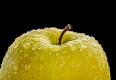 Macro jaune de pomme couvert de baisses de l'eau Photographie stock libre de droits