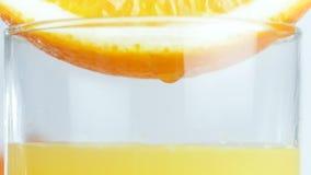 Macro4k video van sap oranje plak in glas Dalingen die van sap neer vallen stock footage