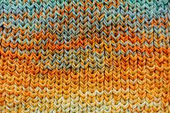 Macro Knitted scarf with colorful melange threads. Woman Knitting a scarf. Hands holding threads. Colorfull Knitting with colorful melange threads royalty free stock photos