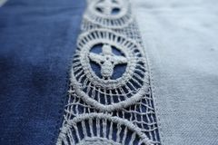 Macro of lace on blue fabric. Macro of lace on blue linen fabric Royalty Free Stock Images