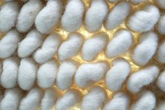 Macro of large white woven background with yellow light showing though woven fibers inbetween poofs. A Macro of large white woven background with yellow light Royalty Free Stock Photos
