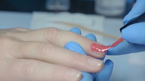 Macro, Manicure Master Deals Red Lacquer Layer on Woman`s Fingernail. Macro, Manicure Master Deals Red Lacquer Layer on Women Nail at Beauty Salon stock video footage