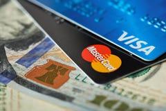 Macro of master and  visa card. New york, USA - August 24, 2017: Macro of master and  visa card laying on hundred dollar bill Royalty Free Stock Images
