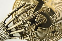 Macro metal monster hand or skeleton on Bitcoin. The concept of piracy with crypto currency. stock photos