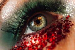 Macro oeil vert avec le bokeh rouge de miroitement Pousse en gros plan créative de lentille de cru, foyer mou Le maquillage miroi photographie stock libre de droits
