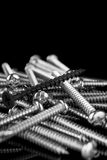 Macro, one black screw in a pile of brass screws Stock Image