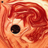 Abstract mixture of pearlescent red and orange pigments. Macro of orange and red pigments mixed with oil arranged in a vortex shape with a black spot Royalty Free Stock Images