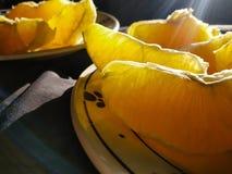 Macro oranje fruitplakken die op plaat worden gepeld royalty-vrije stock foto's