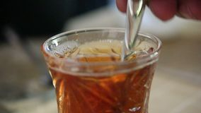 Macro of oriental turkish transparent teacup with hot black tea mix by teaspoon stock footage