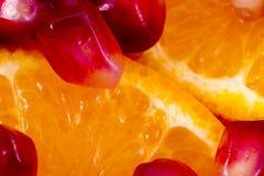 Macro peeled ripe pomegranate fruit with many slices of orange f Stock Images