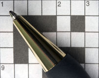 Macro pen and crossword puzzle. A macro image of a pen pointing to the first clue to solve in a crossword puzzle Royalty Free Stock Photography