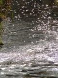 Macro photo avec une texture décorative de fond de lumière du soleil de l'eau et des bulles sur la surface de l'eau de la rivière Photographie stock libre de droits