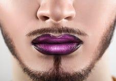 Macro photo of bearded male lips with makeup Stock Photo