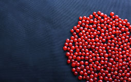 Macro photo of bright red and fresh currant on a dark blue fabric. Ripe and juicy currant on a dark background. Sweet berries. Stock Photography