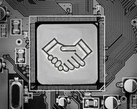 Metal Wheel Concept. Macro photo of circuit board with handshake sign on the chip surface; electronic deal concept Stock Photography