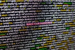 Macro photo of computer screen with program source code and highlighted HIJACK YOUR PASSWORDS inscription in the middle Royalty Free Stock Photos