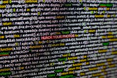 Macro photo of computer screen with program source code and highlighted HIJACK YOUR PHOTOS inscription in the middle Royalty Free Stock Image