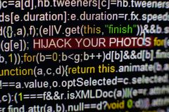 Macro photo of computer screen with program source code and highlighted HIJACK YOUR PHOTOS inscription in the middle Stock Photography