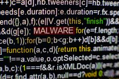 Macro photo of computer screen with program source code and highlighted MALWARE inscription in the middle. Script on the Stock Photos