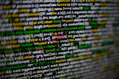 Macro photo of computer screen with program source code and highlighted SPYWARE inscription in the middle. Script on the Royalty Free Stock Photo
